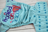 Seaspray Hooked on Daddy WITH GLITTER (seaspray outer, imperial inner, two toned snaps; imperial caps, aqua pieces)<br>Embroidered, One Size Pocket Diaper<br>Instock and Ready to Ship