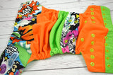 Grafitti (spring green inner, two toned snaps; orange caps, apple pieces) <br>Boutique Scrappy, One Size Pocket Diaper<br>Instock and Ready to Ship