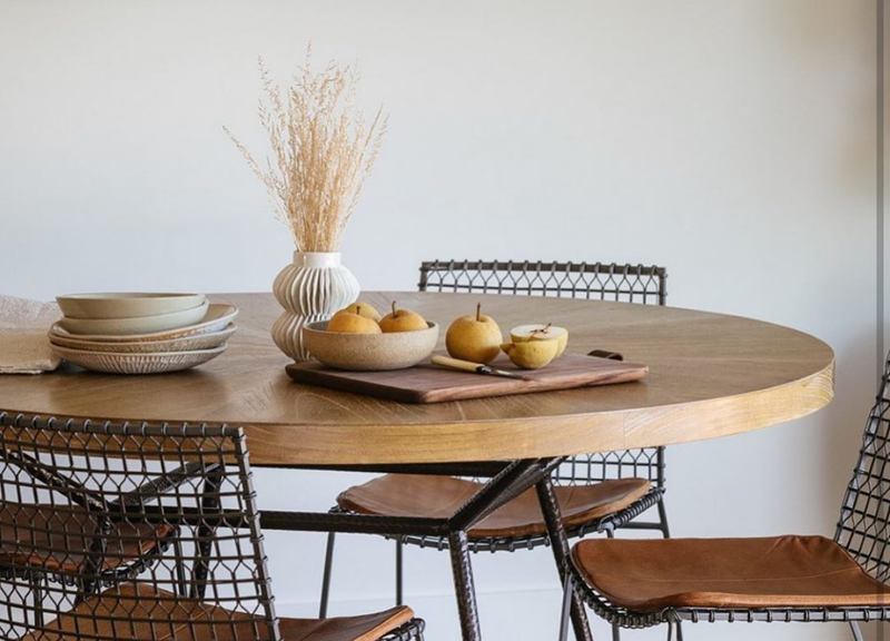 Photo of modern wooden table with wire chairs and vintage ceramics. We rent our vintage.