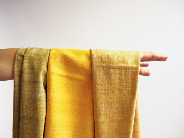 Scarf made from organic peace silk on a handloom in India. Eri silk scarf from India handspun and handwoven in a warm yellow color. Naturally dyed with the jackfruit bark. Organic and natural material, 100% peace silk. Slow and ethically made.