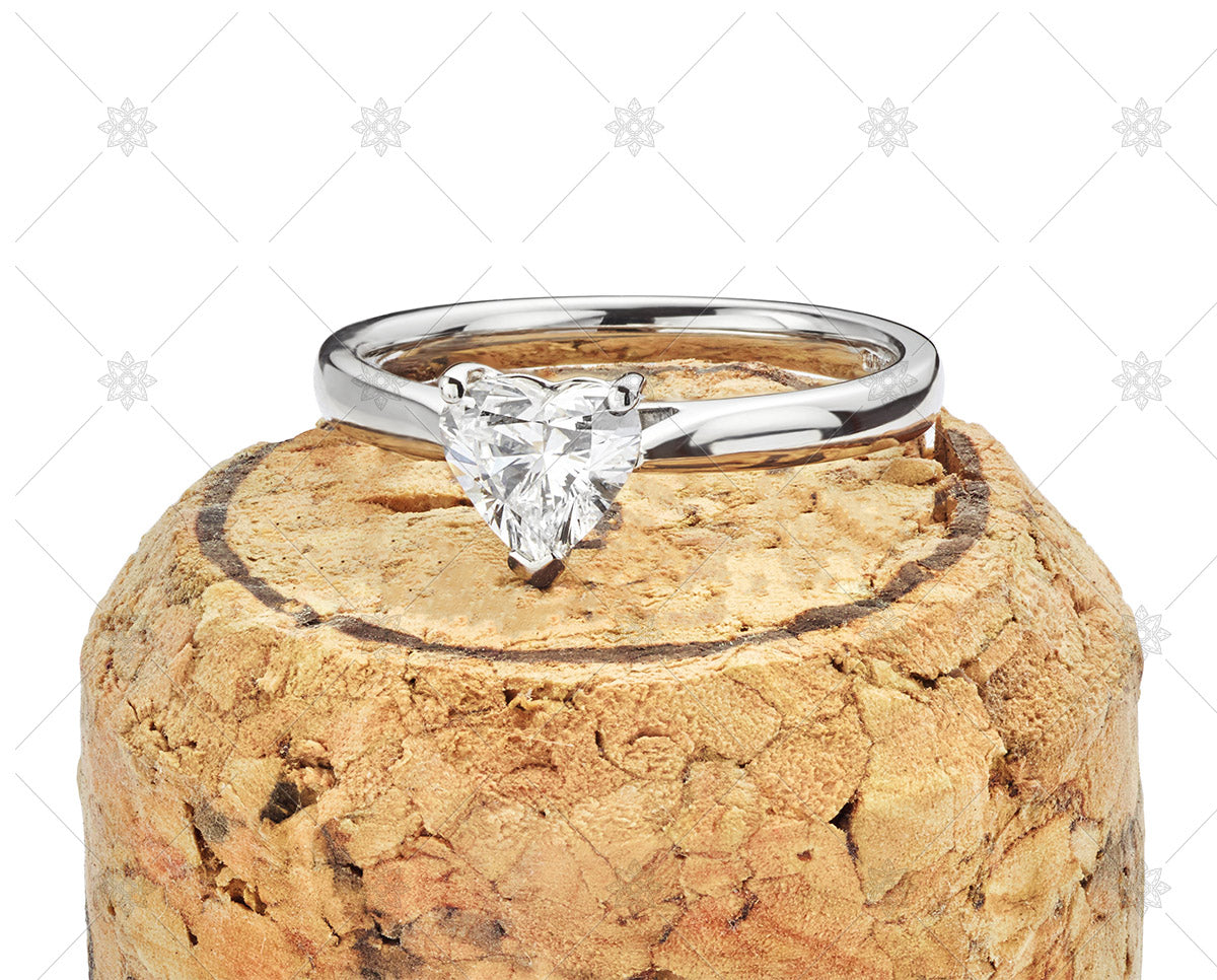 Heart shaped diamond white gold ring ontop of a cork
