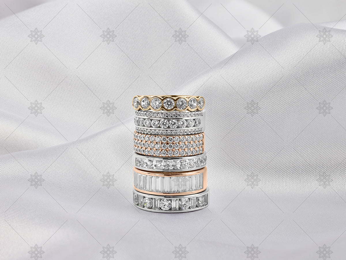 gold eternity ring stack on white silk background