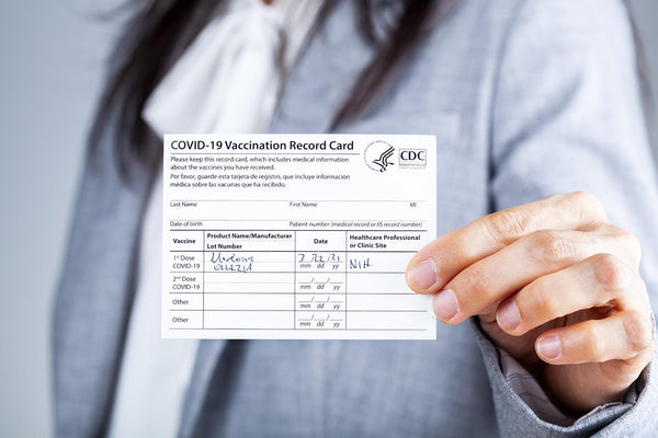Woman holding Covid 19 Vaccine card