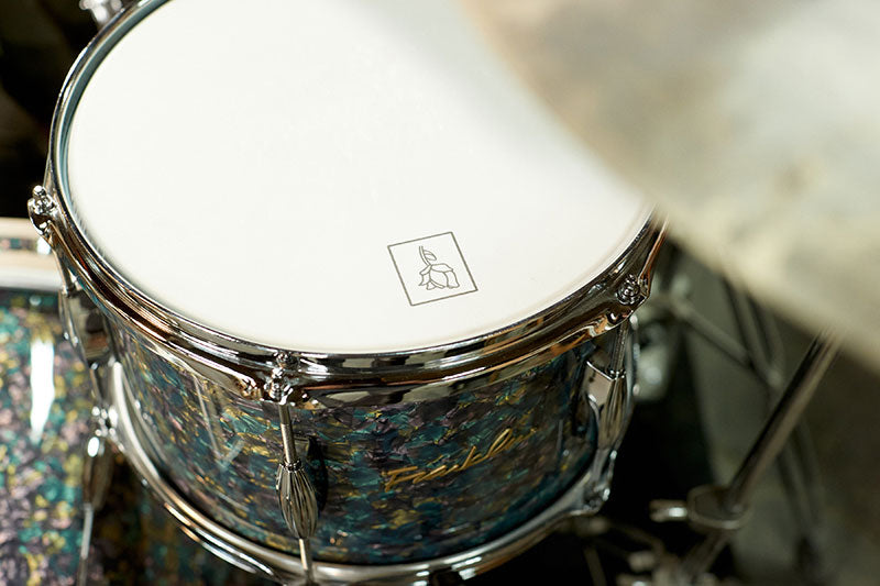 Close up of logo shaped like a rose on the drum head.