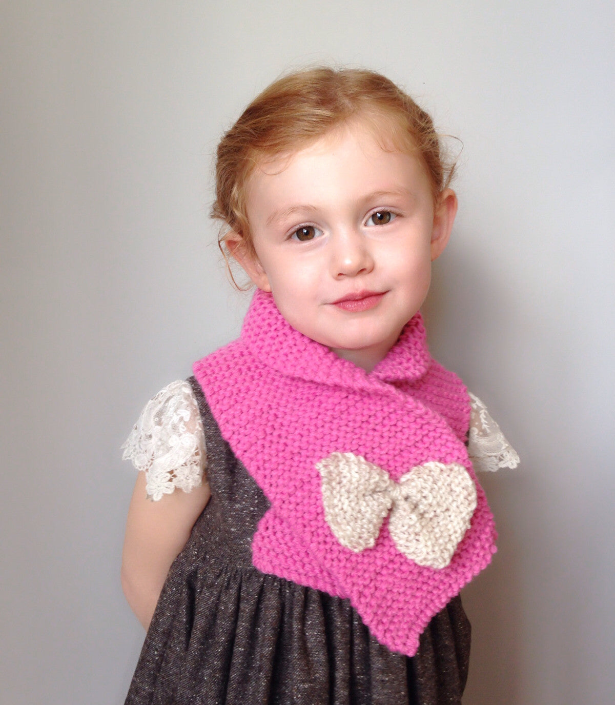 Hand knit scarf in bright pink with oatmeal bow