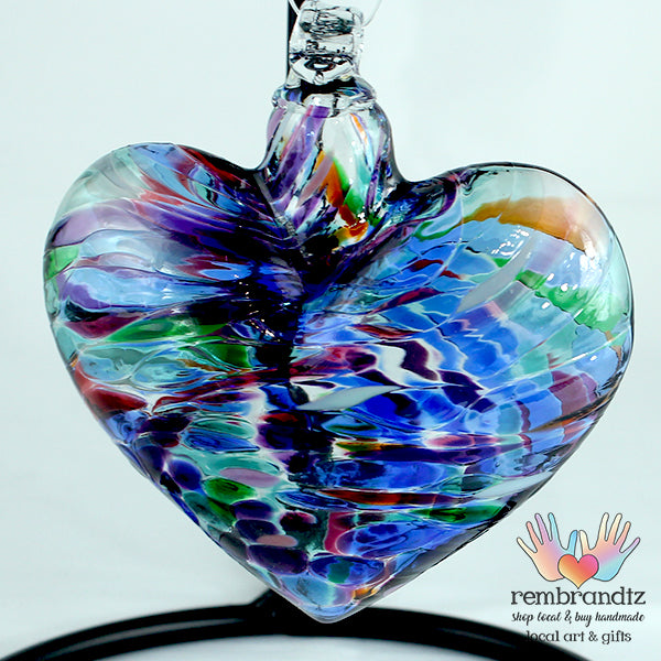Classic Multi Handmade Glass Heart, with Blues, Green and Purples swirled in the hand blown glass, ready to hang in a sunny window