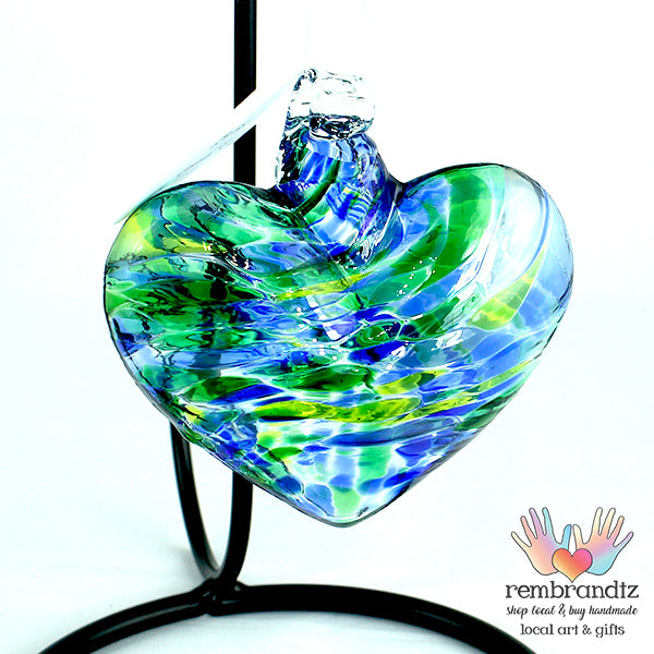 Oceania Hand blown Glass Heart ornament, with swirls of blue and green, ready to hang in a sunny window
