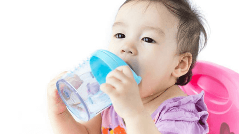 a baby using a sippy cup, how to introduce sippy cup, introducing sippy cup | The Spoiled Mama