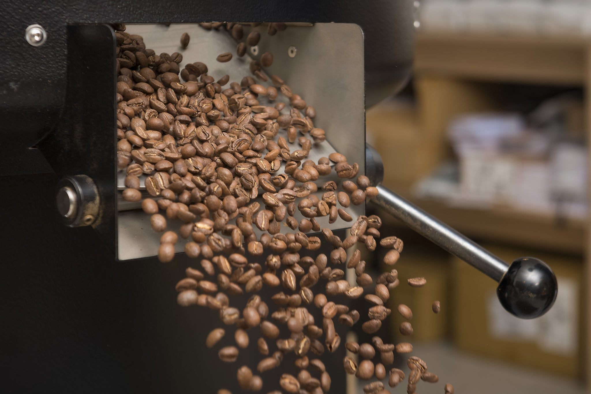 Coffee beans falling out of a roasting machine