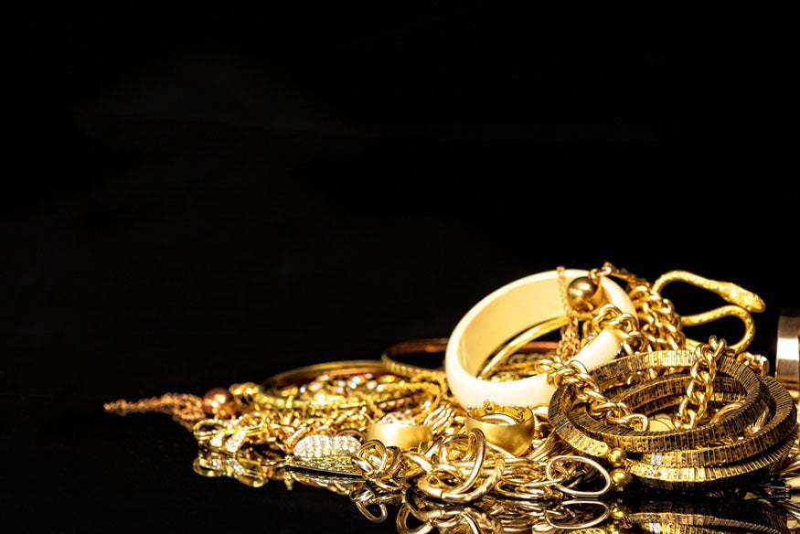 bunch of gold jewelry on black background