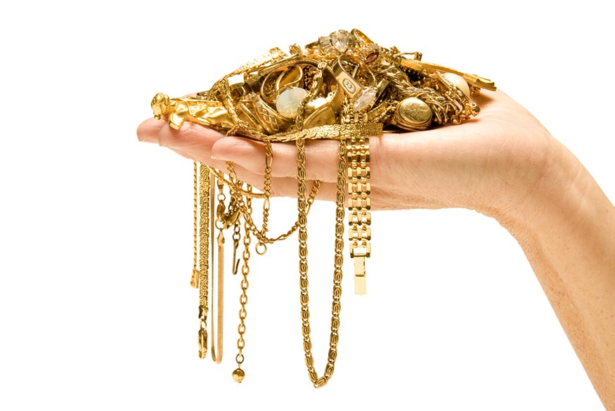 hand holding pile of gold jewelry