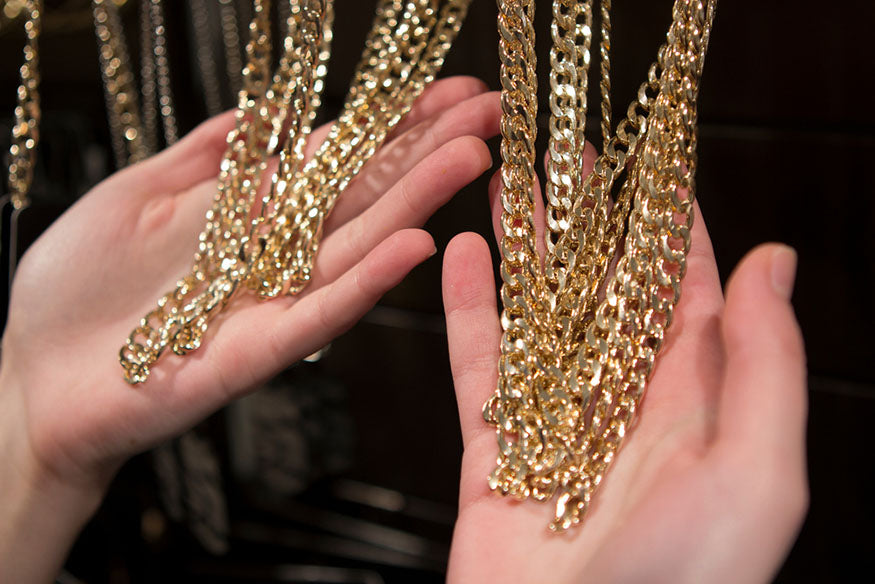 hands holding gold chains