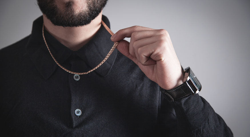 man holding gold chain from neck