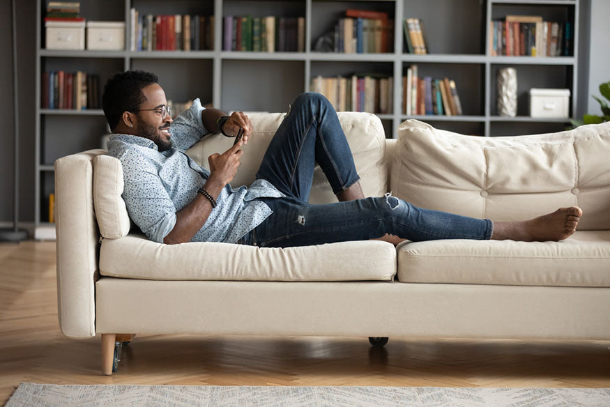 man lounging on couch with phone