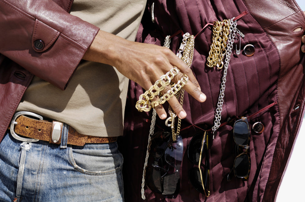 man selling jewelry inside of a jacket