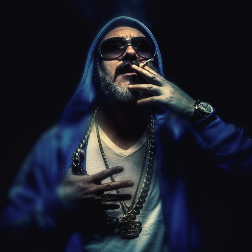 Portrait of an older man smoking a cigar, wearing gold necklaces and blue jacket