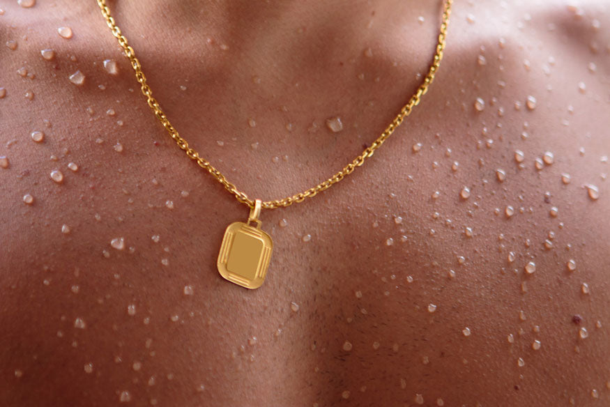 a man wearing a gold chain with a pendant shirtless