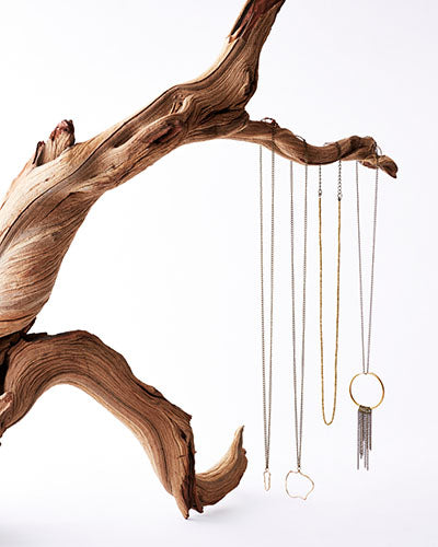 necklaces hanging from twisted driftwood branch