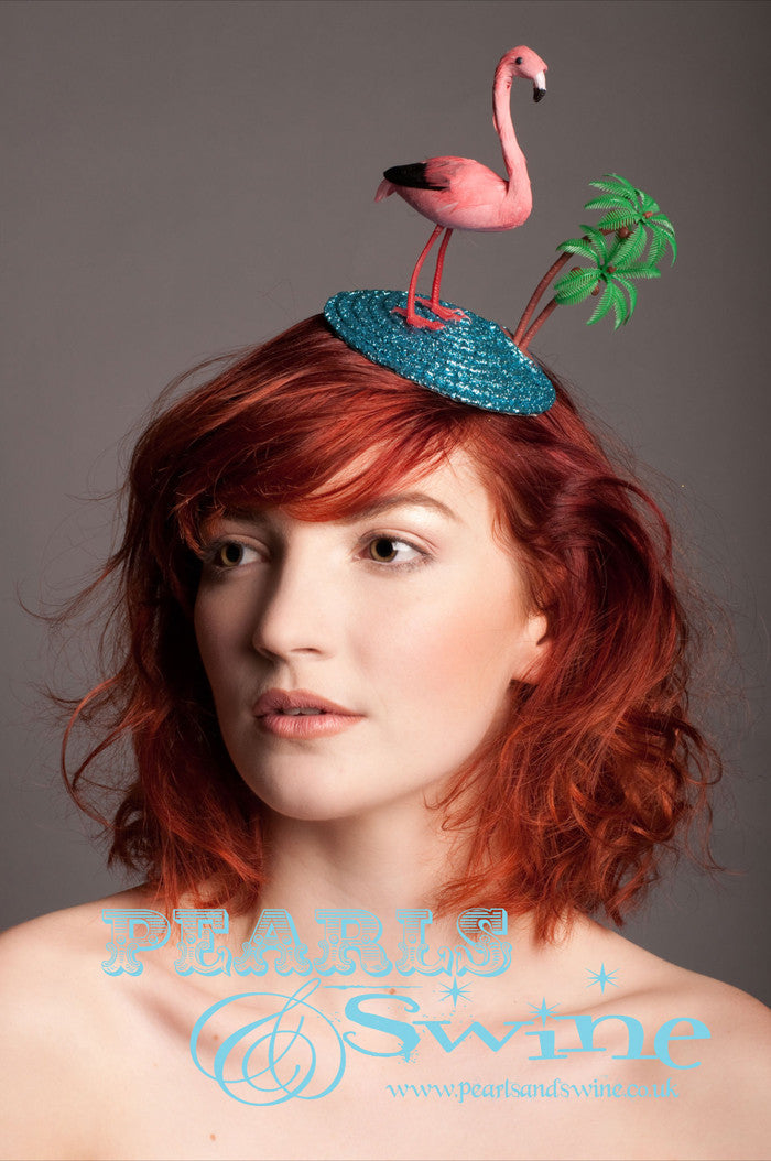 "Tropical Flamingo Fascinator ""Tropicana""   A holiday scene fascinator featuring a pink feathered flamingo, a blue glitter sea and a coconut tree backed with leopard print satin.  Attaches to your hair with a comb"