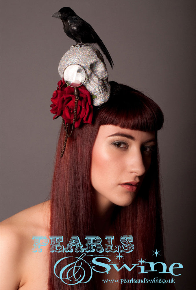 "Skull and Raven Fascinator ""Edgar's Raven""   Diamond glittered skull set on a black glittered base, decorated with a monocle and chain, red velvet roses and a black feathered crow or raven. Inspired by Edgar Allen Poe's ""The Raven"" This is a piece of wearable art which could be displayed in a cabinet when not worn, it is backed with leopard print satin and attaches with a comb and adjustable hat elastic. Perfect for Edgar Allen Poe fans and goth fashion lovers."