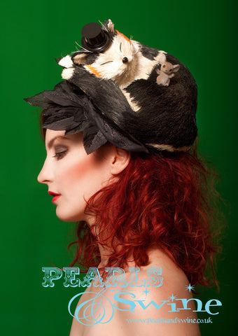 "Sleeping Cat Headpiece ""Sweet Dreams""  Artificial cat, wearing a little top hat. sleeping on a hat decorated with black leaves. There is a cheeky little mouse sat on the snoozing cat. This one of a kind cat hat attaches with a hidden fascinator base that has a comb on it."