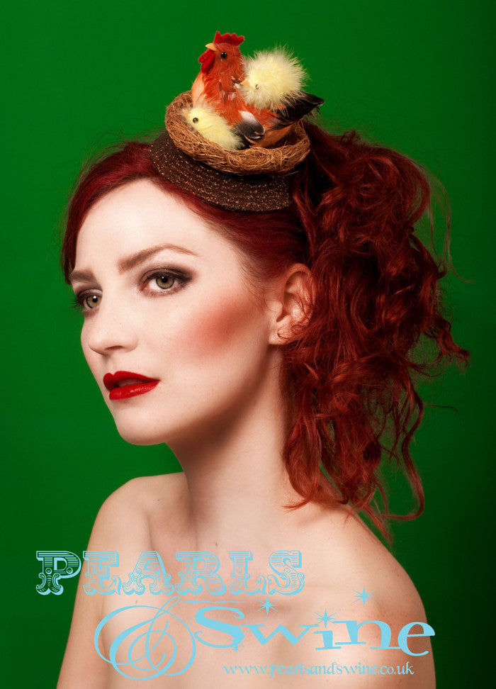 Nest fascinator decorated with a chicken and her fluffy chicks, set on a brown hand glittered base. Backed with a leopard print satin, this attaches with a comb and adjustable hat elastic. This is a cute Easter Bonnet for anyone who loves chickens!