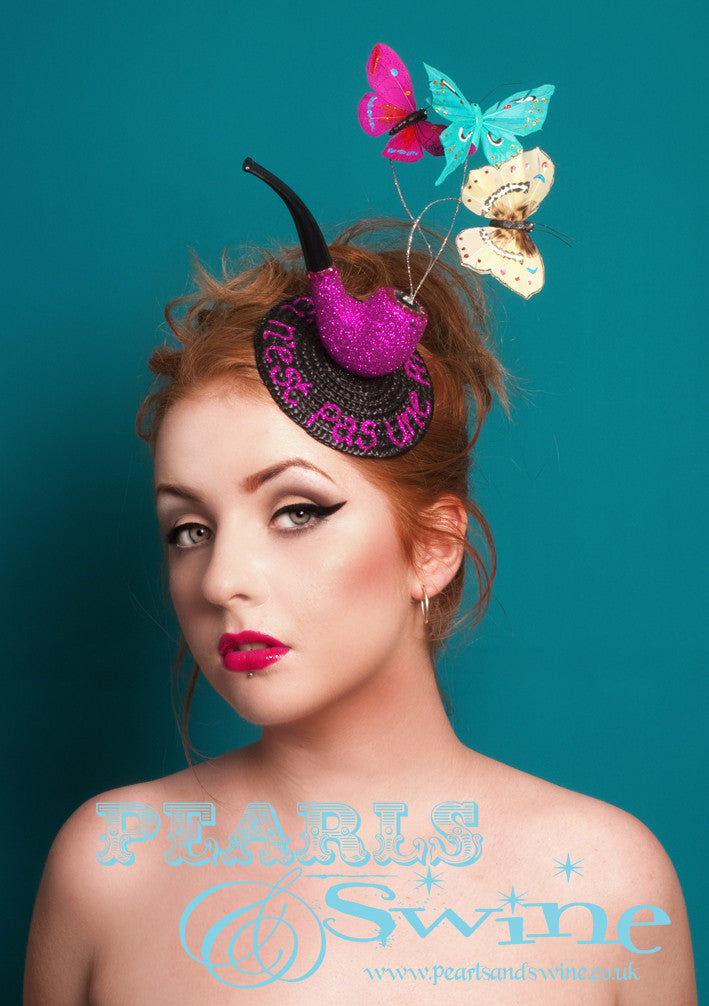 "Tribute to ""Ceci n'est pas une pipe"" by René Magritte, a Belgian surrealist artist aka ""This is not a pipe"". Nope, it's a fascinator...  Surreal lack fascinator base decorated with a pink glittered pipe, silver glittered wires with colourful butterflies (which come to life and move when you wear this) and the words ""Ceci n'est pas une pipe"" in pink glitter. This headpiece is backed in leopard print satin and attaches with a comb and adjustable hat elastic.  Perfect for fans of René Magritte's art."