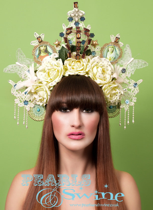 "Virgin Mary Headdress ""Sacrament""  Virgin Mary-inspired headdress which includes an iridescent ivory, glittered lace halo, roses, doves, a gold glittered crown, an image of the Virgin Mary and Jesus, butterflies, stars, Jesus-imprinted wooden beads, crystals, and pearl bead fringes. Set on a headband which is decorated with leaves."