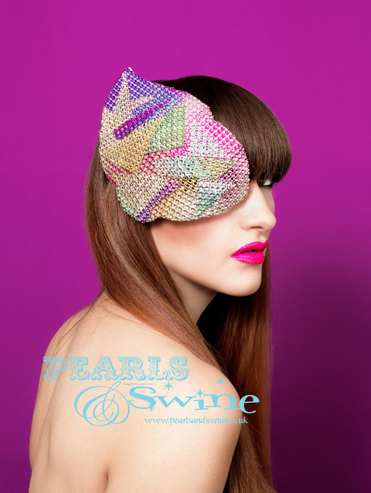 Sparkly rainbow metallic mesh covered, glam rock inspired half mask fascinator which you can also wear as an elaborate eyepatch! You can't see in but you can see out. This mask is blocked by hand and backed with leopard print satin and attaches with a comb and adjustable hat elastic. I love how space age/glam rock/David Bowie/70s/80's this mask is, it's a really unique fashion statement.