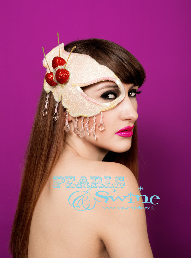 Cherries and cream half mask fascinator covered with iridescent glitter, topped with red glittered cherries, edged in sequins, and dripping with pale pink fringe beading. The mask base is blocked by hand and backed with leopard print satin, it attaches with a comb and adjustable hat elastic. This sparkly cake inspired headpiece is ideal for Marie Antoinette lovers, a masked ball or a burlesque showgirl.