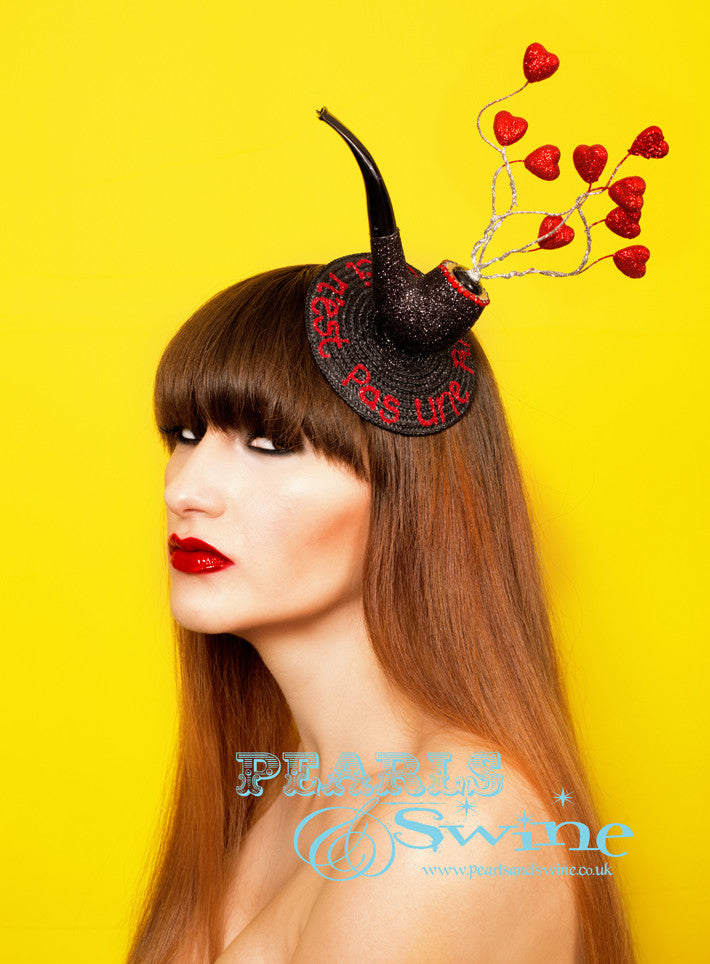 "Surreal Pipe Fascinator ""Ceci N'est Pas Une Pipe""  This surreal pipe fascinator in black glitter, edged with red crystals, silver glittered wire 'smoke' and red glitter hearts set on a fascinator base with  ""Ceci N'est Pas Une Pipe"" in red glitter. Attaches with a comb and hat elastic.  This quirky headpiece is part of a collection of pipe headpieces. Inspired by ""Ceci n'est pas une pipe"" by René Magritte, a Belgian surrealist artist aka ""This is not a pipe"". Nope, it's a fascinator...  Perfect for fans of René Magritte's art."