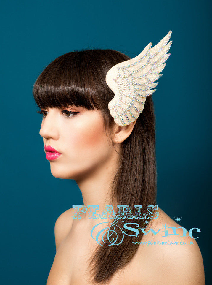 Iridescent glitter wing fascinator edged with feather detailing done in rainbow crystals. Hand blocked and backed with ivory satin, attaches to the hair with a comb and adjustable hat elastic. A perfect bridal headpiece, inspired by Icarus who flew too close to the sun.