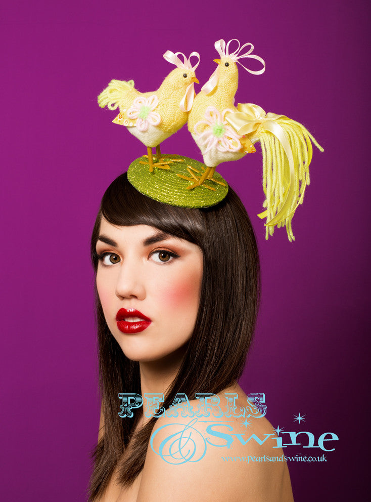 Lime green glitter fascinator decorated with a yellow, knitted chicken and rooster. The base backed with leopard-print satin. Attaches with a comb and adjustable hat elastic.  This is a perfect quirky Easter bonnet, ideal for someone who loves chickens.