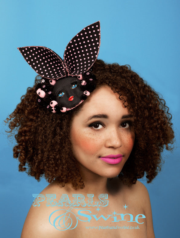 Black vintage doll face fascinator decorated with crystals, pompoms, 3D eyelashes and pink & black polka dot bunny ears edged in a pale pink glitter. Set on a fascinator base this headpiece attaches with a comb and adjustable hat elastic. This whimsical fascinator perfect for Ladies Day at Royal Ascot, it would also make a unique bridal headpiece for an avant garde bride. Suitable for display as a piece of wearable art.