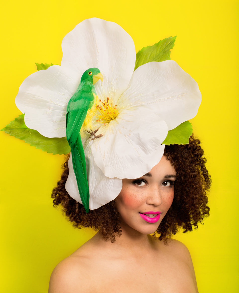Giant tropical sparkly ivory flower with green parrot perched on it. This is set on a fascinator base decorated with leaves.This attaches with a comb and adjustable hat elastic, this is comfortable for all day wearing.  Perfect for Ladies Day at Royal Ascot or a wedding or rock & roll bride.
