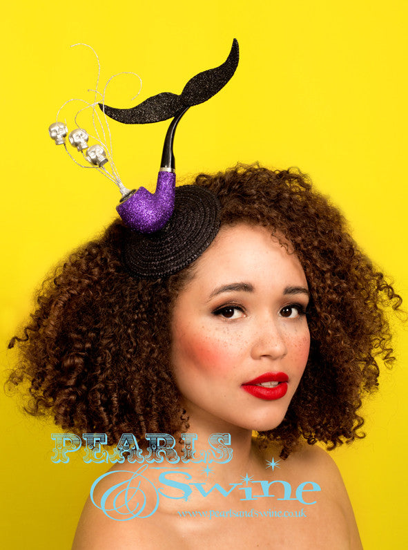 "Surreal Pipe Headpiece ""El Señor de la Muerte""  A fabulously quirky, surreal pipe headpiece set on a fascinator base featuring a sparkling purple pipe with a black glittered moustache, silver glitter smoke, and silver skulls. Attaches with a comb and adjustable hat elastic.  This quirky headpiece is part of a collection of pipe headpieces. Inspired by ""Ceci n'est pas une pipe"" by René Magritte, a Belgian surrealist artist aka ""This is not a pipe"". Nope, it's a fascinator...  Perfect for fans of René Magritte's art."