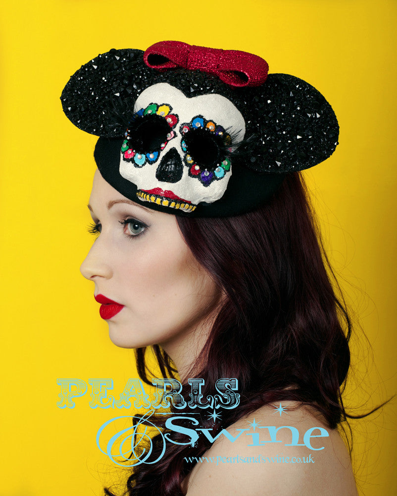 This mouse hat is inspired by the Mexican Day of the Dead. It has a glittered, hand-painted crystal skull with long 3D eyelashes, black gem covered mouse ears and a red glitter bow on a black vintage-style felt hat base. Attaches with a comb and adjustable hat elastic.  The hat also doubles as a piece of art that you can display in a cabinet or on your wall. I recommend keeping it free of dust as it's heavily glittered but it's too pretty to keep hidden away. Perfect for Royal Ascot Ladies Day.
