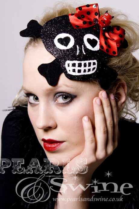 This black glitter skull with cross-bones shaped fascinator decorated with a red bow with devil head and sequins Backed with leopard-print satin, the black glitter skull fascinator attaches with a comb and adjustable hat elastic.