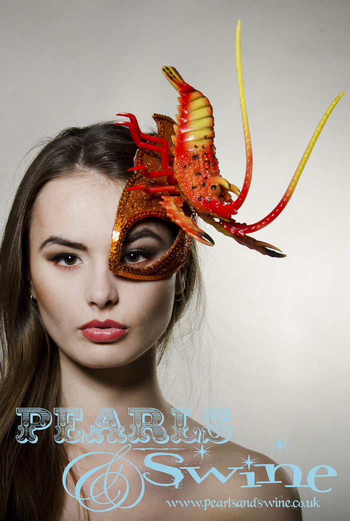 Orange glitter surreal lobster half mask fascinator creation is inspired by Salvador Dali. Made using hand blocked millinery felt backed with leopard print satin fabric, edged with orange sequin and sprinkled with orange crystals. The lobster is sprinkled in orange crystals, the feelers that move when you wear this so you bring the lobster to life. Attaches with a comb, extra bobby pins will help keep firmly in place.
