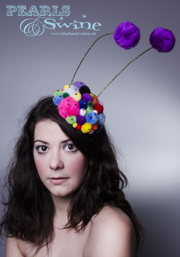 Unusual lime glittered feelers on a pompom covered base, sprinkled in multi coloured crystals. This pom pom feelers headpiece base is backed with leopard print satin. Attaches with a comb and adjustable hat elastic.