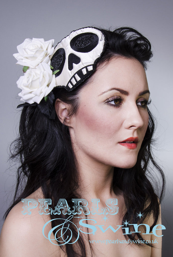 Ivory skull fascinator, edged and decorated with black glitter and ivory velvet roses. Set on a black straw base, attaches with a comb and adjustable hat elastic.   Perfect for day of the dead, goth and Halloween fashion lovers!