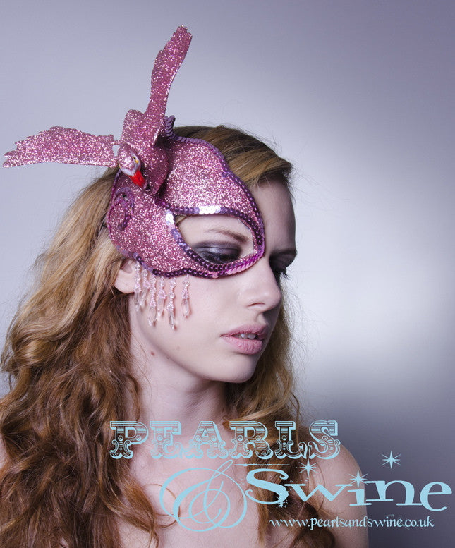 The flamingo half mask fascinator features a candy pink glittered flamingo, set on a hand blocked half mask, edged in pink gems, dripping with pink fringe beading and backed with leopard print satin. Attaches with a comb and adjustable hat elastic.  This half mask fascinator is signature P&S headpiece.  Perfect for a prom, burlesque showgirl or anyone who loves flamingos
