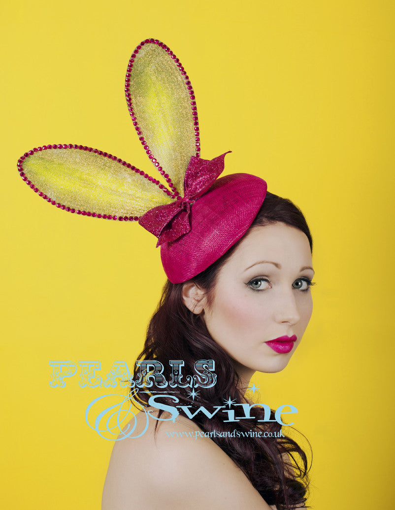 Lime green bunny ears embellished in iridescent gold glitter set on a fuchsia pink sinamay button hat base decorated with a pink glitter bow. This hat attaches with a comb and hat elastic.  This quirky headpiece would be completely at home at Royal Ascot Ladies Day or a Mad Hatters tea party.