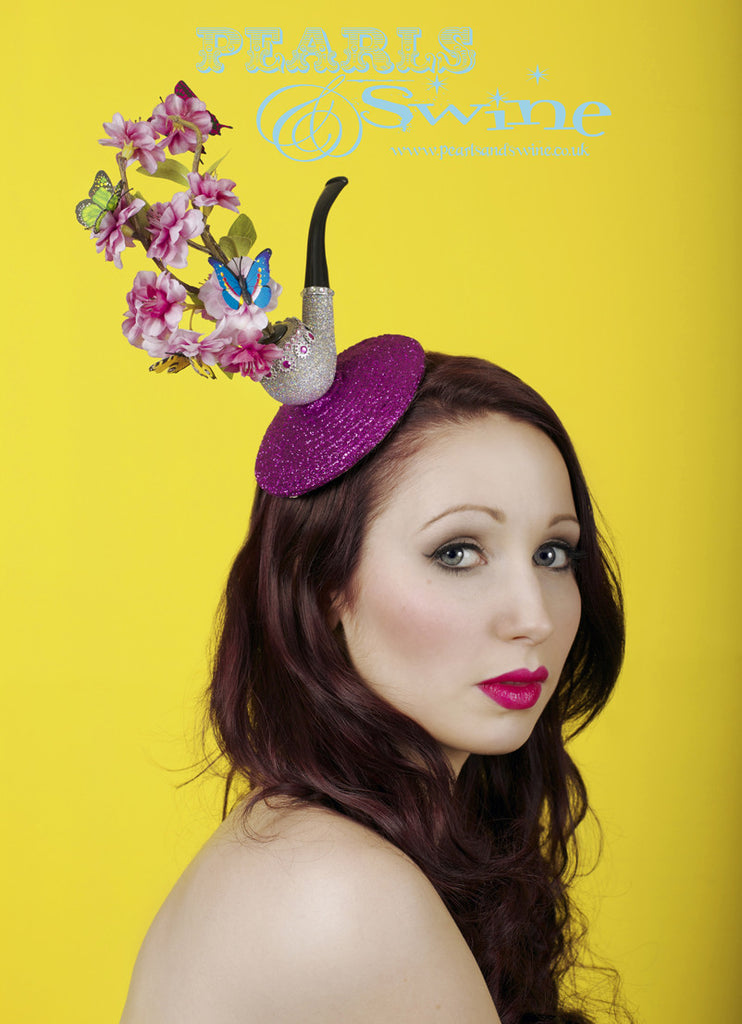 "Butterfly and pipe fascinator, featuring cherry-blossom and butterfly 'smoke' emerging from a sparkly pipe. Set on a fuchsia-pink glitter base, the butterfly and pipe fascinator is backed with satin and attaches with a comb and adjustable hat elastic. ""Opium"" Butterfly & Pipe fascinator is part of my ""This is not a Pipe"" millinery collection inspired by René Magritte. With an 11cm base this is perfect for Royal Ascot, a wedding or lovers of René Magritte's art."