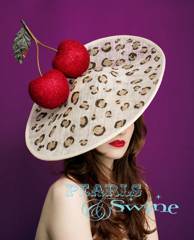 Giant red glittered cherries on a large ivory sinamay hat base which is hand painted with glittered leopard print. This leopard print hat fits all head sizes as it attaches with a wide headband. This headpiece can be made in other colours to match your outfit, just message me to ask.  Giant cherry hats have been the rage for a few years now. This is a unique take on them, its a perfect hat for a wedding or Ladies Day at the Royal Ascot races!