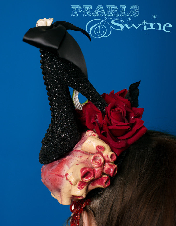 Anatomical heart hat, being crushed by a black glittered high heel shoe, decorated with a skull bow and black gems. This one of a kind, anatomical heart hat also has red velvet roses, a snake, and drips with red fringe beading.  Attaches with a comb and adjustable hat elastic.  This Halloween style hat is perfect for heart-breakers and devil-women. It's a piece of wearable art, a wicked take on Schiaparelli's shoe hat. The sort of Halloween hat you want to keep on display in a glass cabinet all year round.