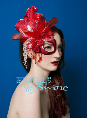 A hand blocked half mask fascinator covered in red glitter, hand stitched pieces of red and white car light, sequin, beading, crystals and a hummingbird bursting out of the explosion. Backed with satin, this attaches with a comb and adjustable hat elastic.