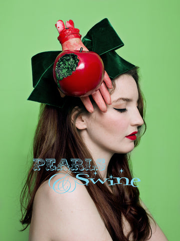 "One of a kind Halloween fascinator, featuring a giant emerald green velvet bow, dismembered hand holding a shiny red bitten apple oozing green glitter ""poison"". Attaches with a comb and adjustable hat elastic."