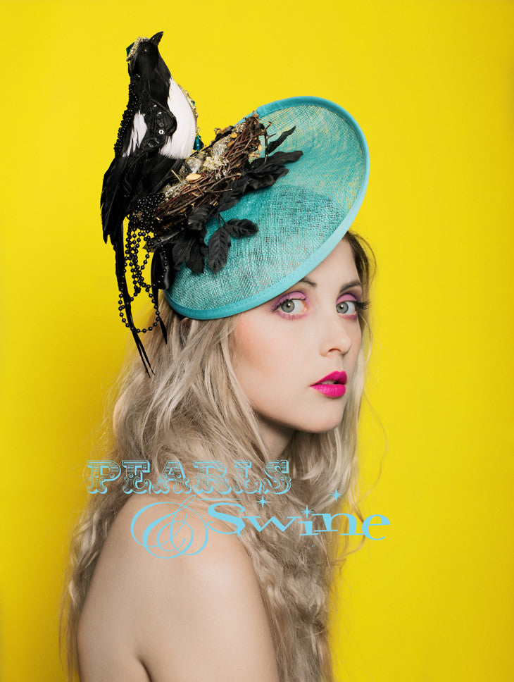 Very detailed, one of a kind artificial magpie in it's nest set on an aqua blue hat. The magpie is decorated with lace, sequin and jewels, perched in a nest strewn with jewels and treasures. This is set on a headband, if needed bobby pins will help to secure firmly to the head.  This hat is perfect for ladies day at Royal Ascot or a wedding.