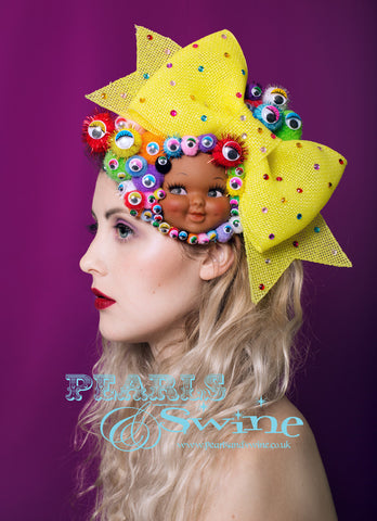 Vintage dimpled doll face fascinator decorated with colourful pompoms, wiggly eyes, a giant yellow glitter bow decorated with gems. All set on a fascinator base which attaches with a comb and adjustable hat elastic. This surreal doll face headpiece is totally eye catching and quirky. Perfect for Royal Ascot Ladies day or a unique bride who wants to make a real statement on her wedding day. This would be fabulous displayed as a piece of art when not worn.